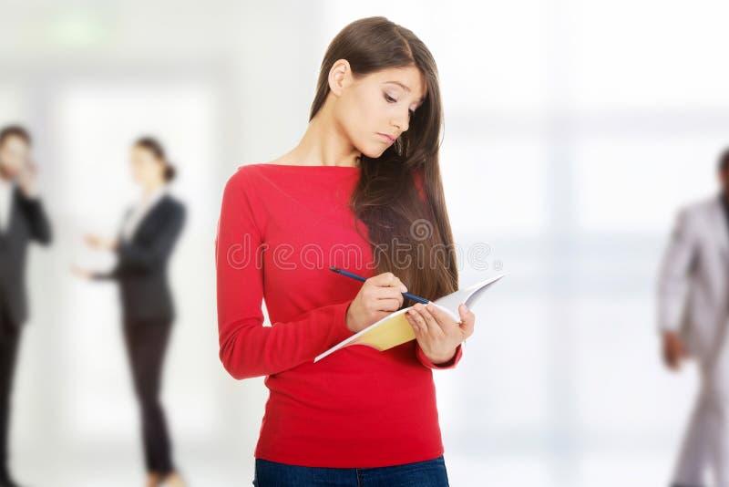 Kvinnlig student med anteckningsboken royaltyfri foto