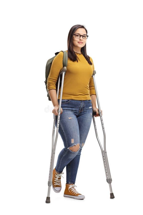 Kvinnlig student med kryckor arkivfoto