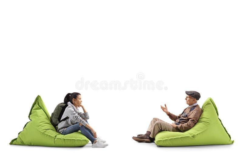 Kvinnlig student och hög en man som sitter på bönapåsar och samtal arkivfoto
