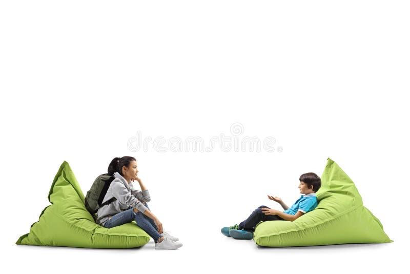 Kvinnlig student och lite pojke som sitter på bönapåsar och samtal arkivfoto