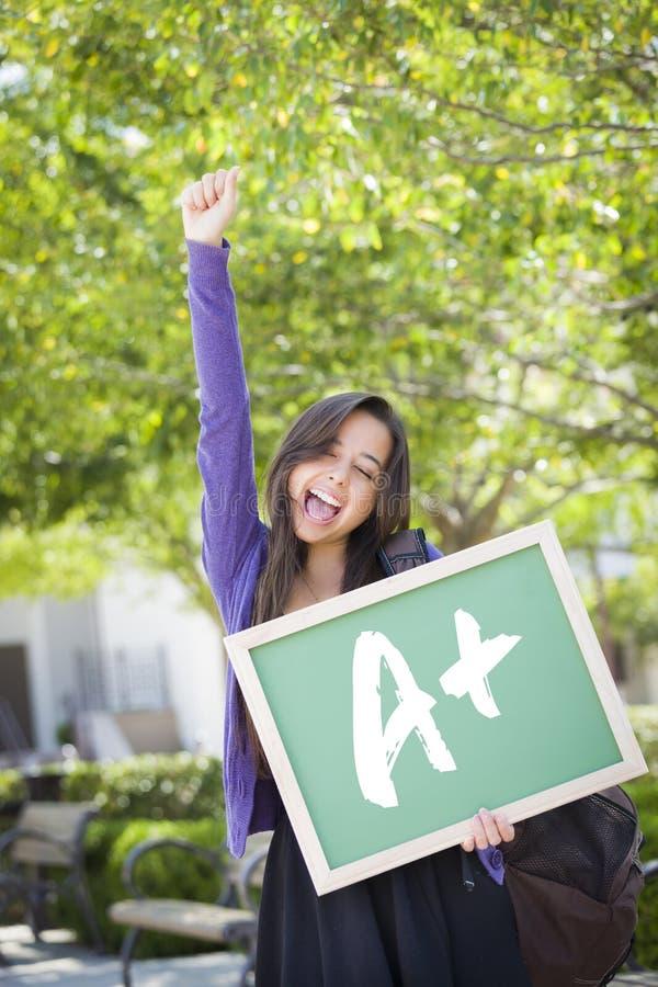 Kvinnlig student skriftliga Holding Chalkboard With A+ för blandat lopp royaltyfria foton