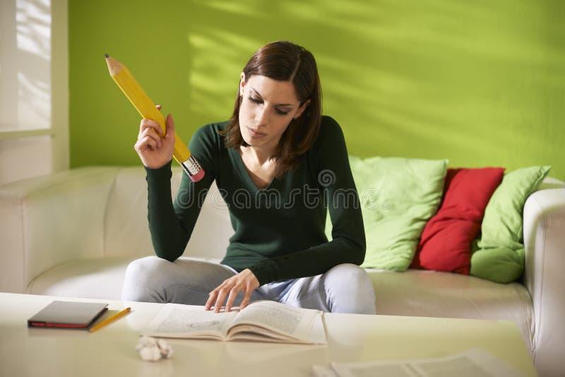 Kvinnlig student som gör läxor med den stora blyertspennan royaltyfria bilder