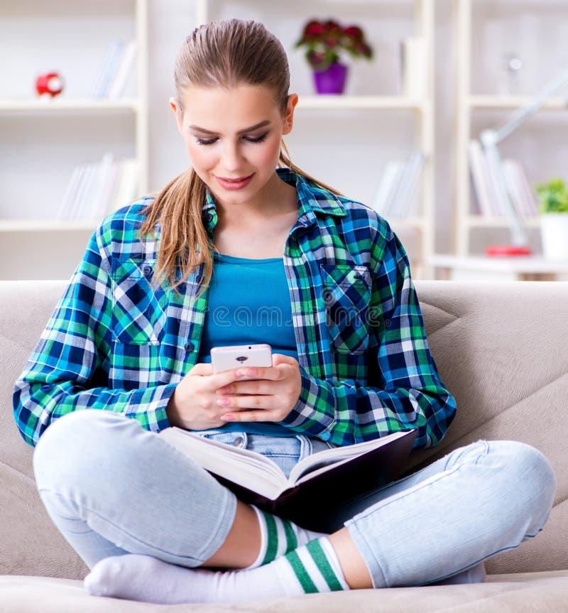 Kvinnlig student som l?ser boksammantr?det p? soffan royaltyfri fotografi