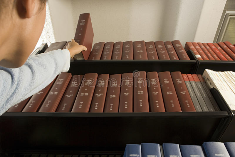 Kvinnlig student som når för en bok arkivbild