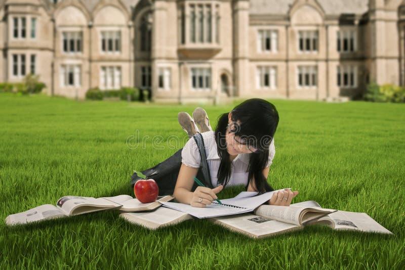 Kvinnlig student som studerar på gräs royaltyfri fotografi