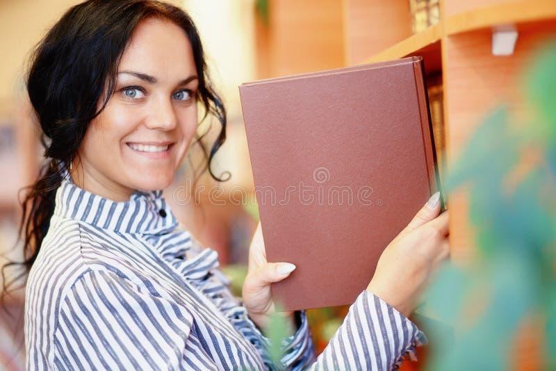 Kvinnlig student som väljer boken från arkivhylla royaltyfria bilder