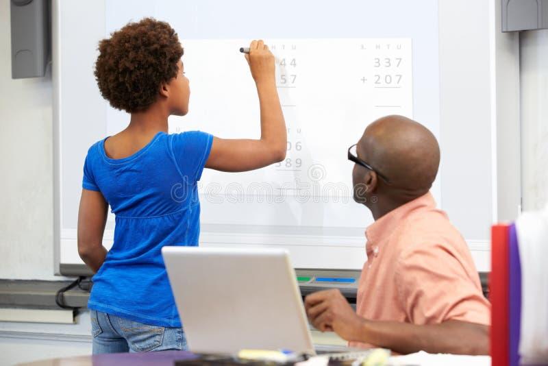 Kvinnlig student Writing Answer On Whiteboard royaltyfri fotografi