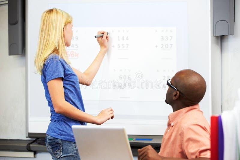 Kvinnlig student Writing Answer On Whiteboard royaltyfria foton