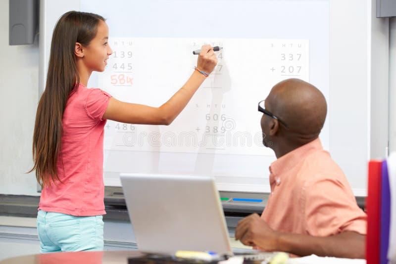 Kvinnlig student Writing Answer On Whiteboard arkivfoton