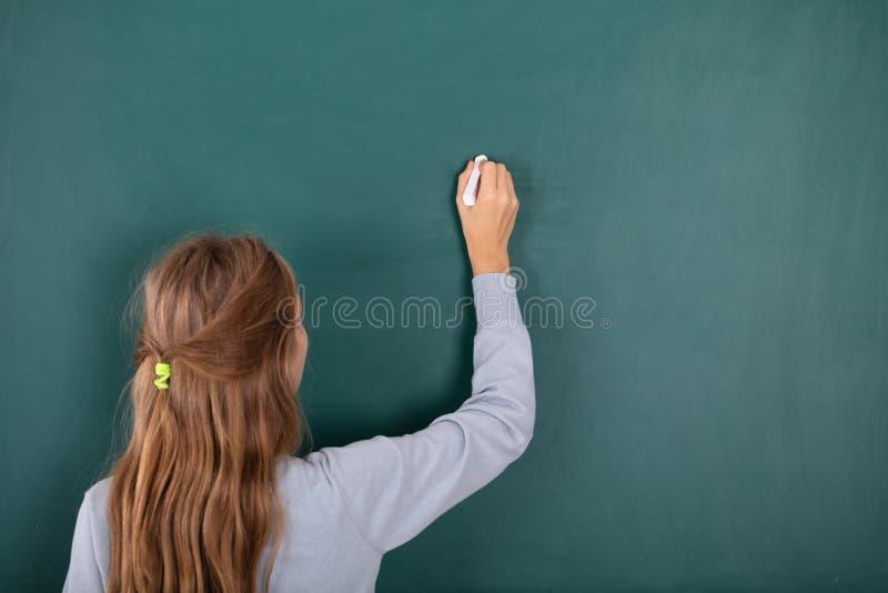 Kvinnlig student Writing With Chalk p? den svart tavlan royaltyfria foton