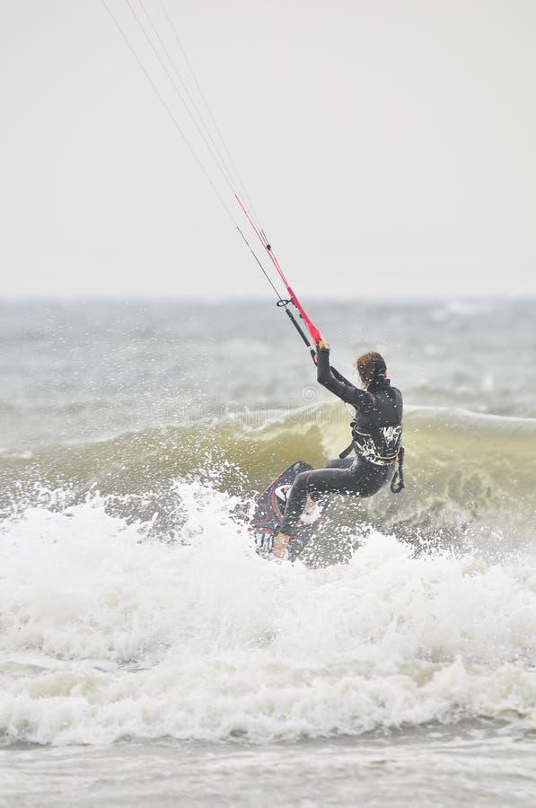 Kvinnlig surfare som kitesurfing i sprej. royaltyfri bild