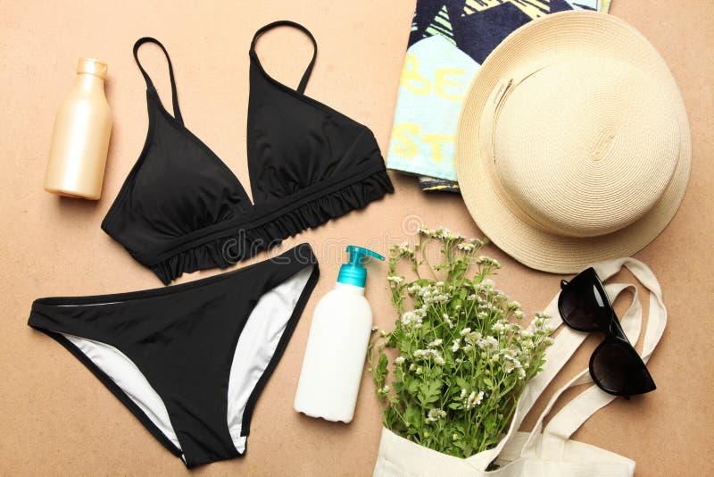 Kvinnlig svart baddräkt, sugrörhatt, strandhandduk arkivbilder