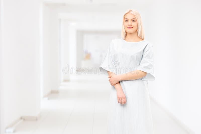 Kvinnlig tålmodig bärande sjukhuskappa och posera i ett sjukhus arkivbild