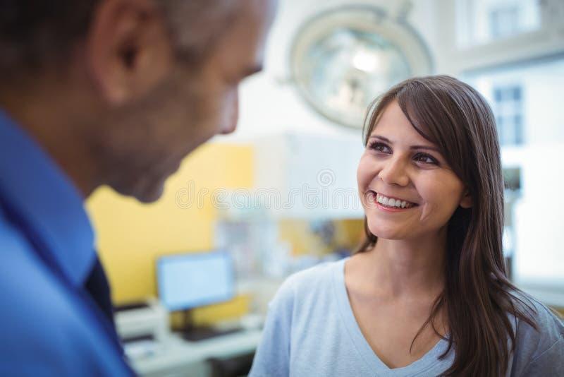 Kvinnlig tålmodig växelverkan med doktorn under besök arkivfoton