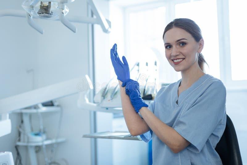 Kvinnlig tandläkare för upptakt som sätter på rubber handskar royaltyfria foton
