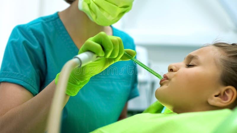 Kvinnlig tandläkare som använder salivhylsutkastaren, tonårs- flicka som sitter, i att rynka pannan för stol royaltyfria bilder