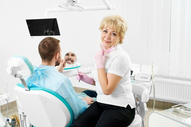 Kvinnlig tandläkare som rymmer en spegel för en manlig klient av en tandläkekonst som ler kontrollera hans tänder arkivbild