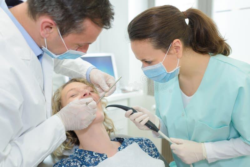 Kvinnlig tandläkare som skakar händer med kvinnan i tandläkarestol royaltyfria bilder