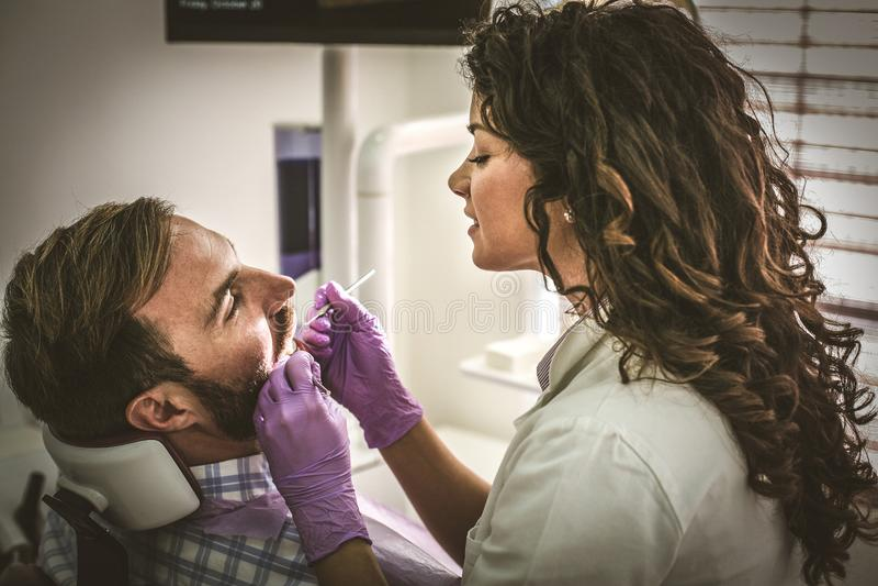 Kvinnlig tandläkare som undersöker den unga mannen arkivbild