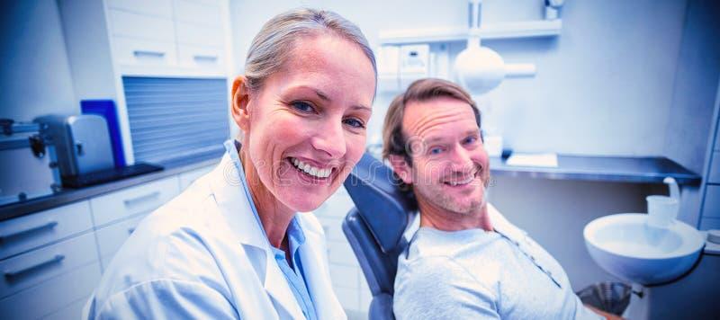 Kvinnlig tandläkarehandstil på skrivplattan, medan påverka varandra med den manliga patienten royaltyfria foton