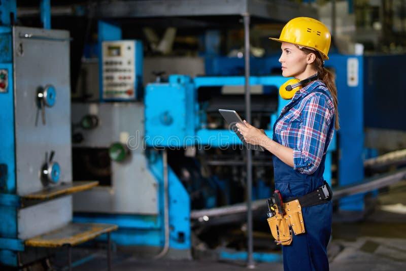 Kvinnlig tekniker Checking Machines på fabriken royaltyfri fotografi