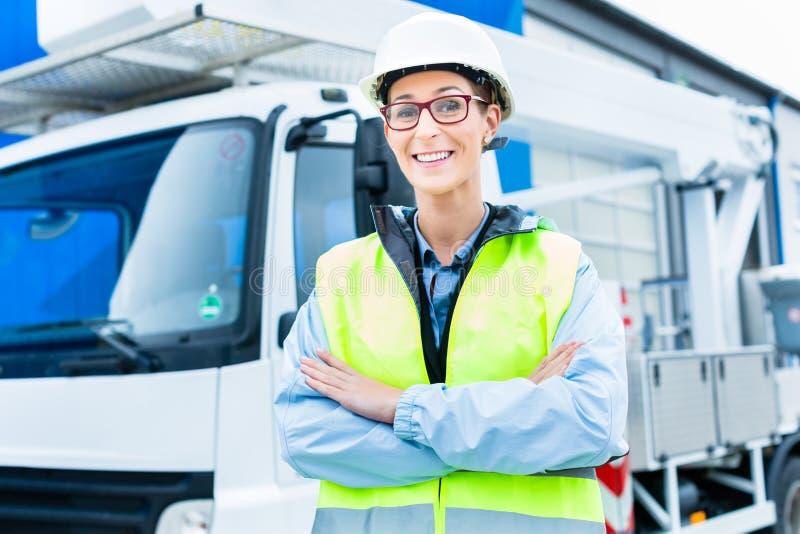 Kvinnlig tekniker framme av lastbilen på plats arkivfoto