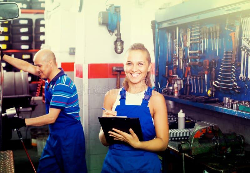 Kvinnlig tekniker i overaller som rymmer skrivplattan i bilseminarium royaltyfri foto