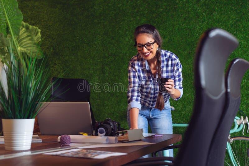 Kvinnlig tekniker som arbetar i hennes kontor med en kopp kaffe i händer arkivbild