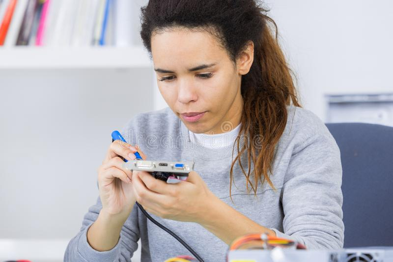 Kvinnlig tekniker som arbetar med transistorn arkivfoto
