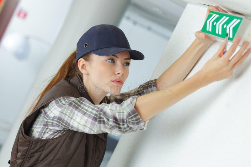 Kvinnlig tekniker som installerar utgångstecknet, i byggande royaltyfria foton