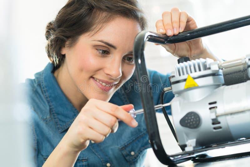 Kvinnlig tekniker som reparerar maskinen royaltyfri bild
