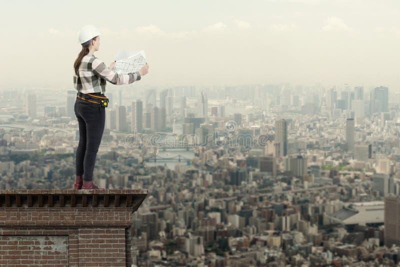 Kvinnlig tekniker som rymmer konstruktionsplan som står på taköverkanten ovanför en stad arkivbilder