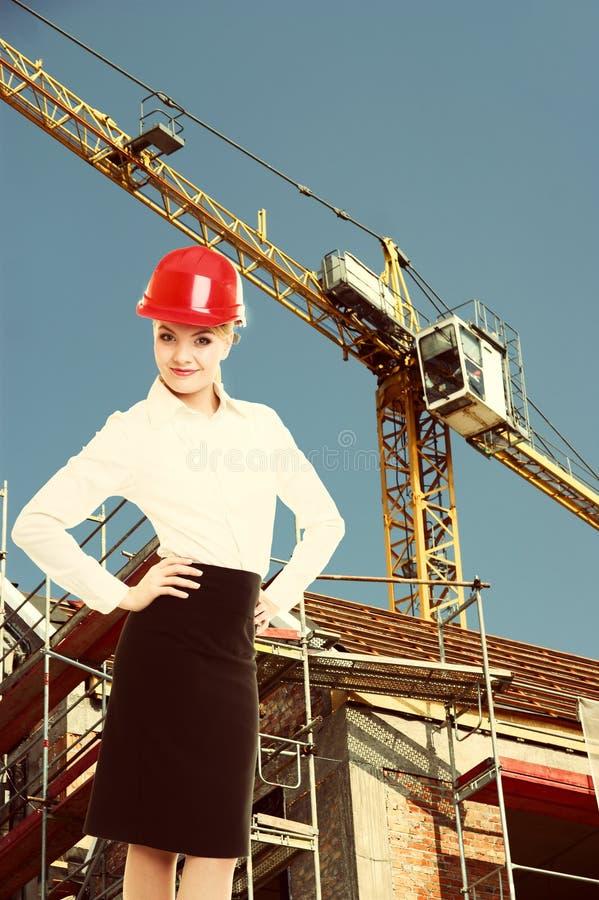 Kvinnlig teknikerkvinna i röd säkerhetshjälm på konstruktionsplats royaltyfria foton