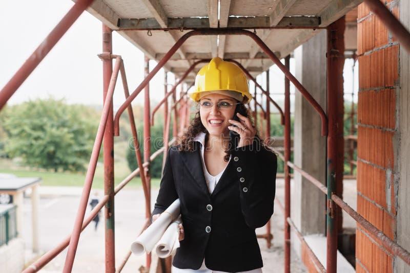 Kvinnlig teknikerTalking On Mobile telefon i konstruktionsplats arkivfoton
