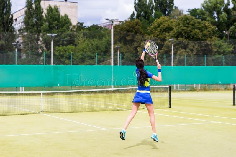 Kvinnlig tennisspelare i handling på en utomhus- domstol royaltyfri bild