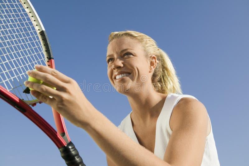 Kvinnlig tennisspelare som förbereder sig att tjäna som upp slut för sikt för låg vinkel fotografering för bildbyråer