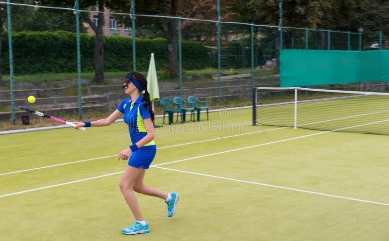 Kvinnlig tennisspelare som värmer upp för tennismatch på en domstolnolla arkivfoton