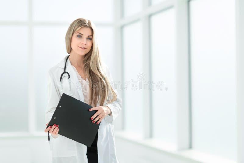 Kvinnlig terapeut med en skrivplatta som står nära sjukhusfönstret arkivbild