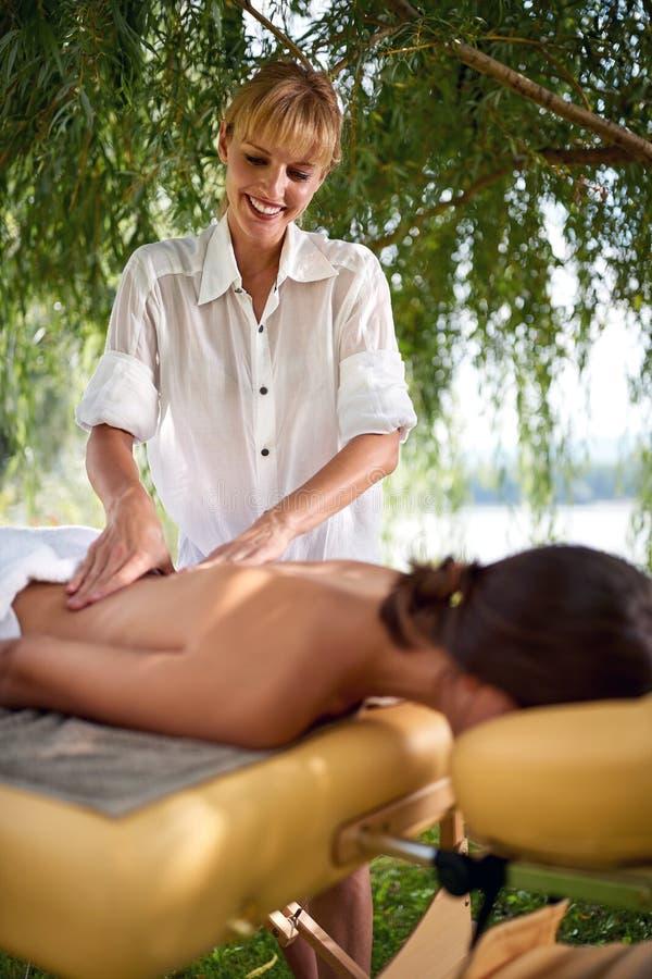 Kvinnlig terapeut som gör den utomhus- massagen royaltyfri foto