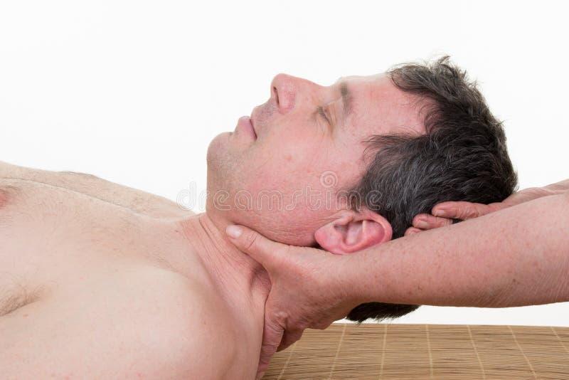 Kvinnlig terapeut som masserar halsen av kvinnan, medan rymma hennes huvud i ett rum royaltyfri fotografi