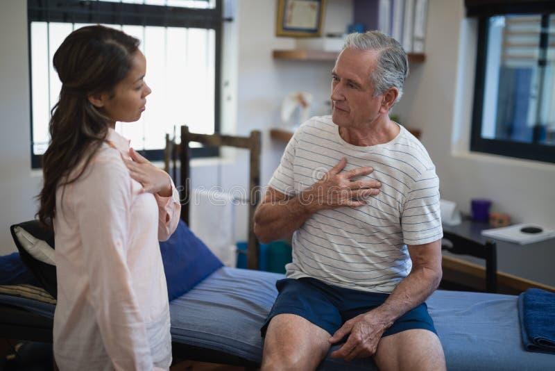 Kvinnlig terapeut som talar med den höga manliga patienten royaltyfria bilder