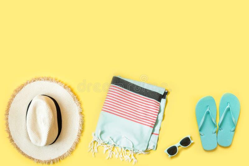 Kvinnlig tillbehör för strand, sugrörstrandhatt, handduk, solglasögon på guling Utrymme f?r text Tropisk semester f?r sommar arkivfoto