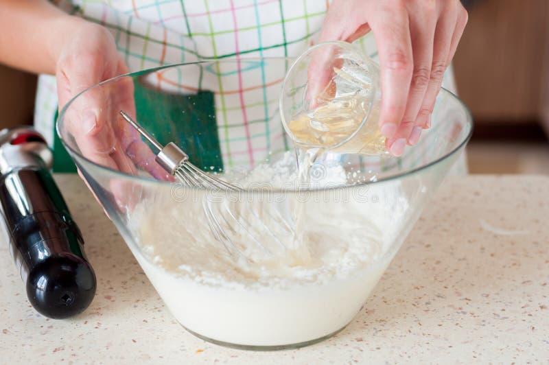 Kvinnlig tillfoga gelatin till ostkakablandningen royaltyfria bilder