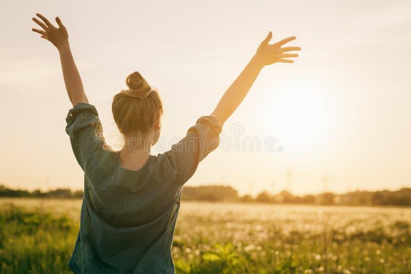 Kvinnlig tonårig frihet för flickaställningskänsel med armar som sträcks till himlen fotografering för bildbyråer