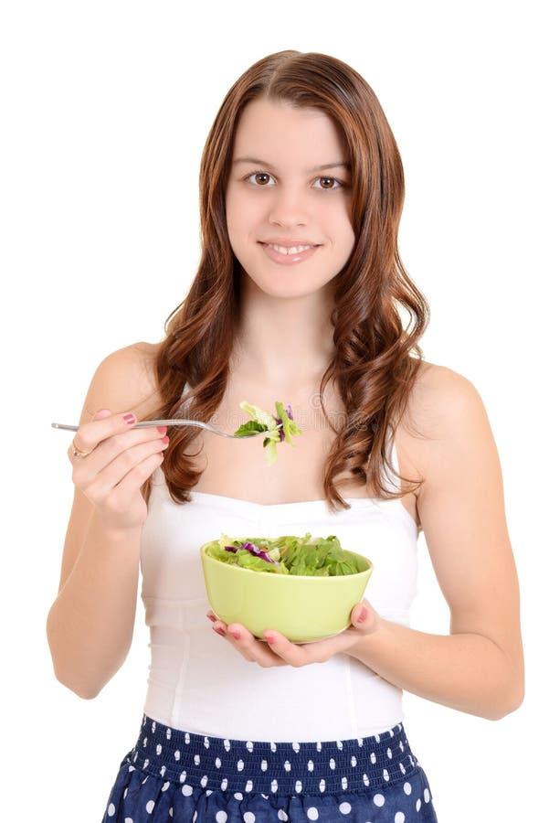 Kvinnlig tonåring som äter sallad arkivbild