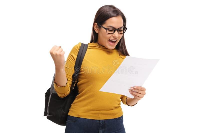 Kvinnlig tonårs- student som ser en examen och gör en gest happines royaltyfri fotografi