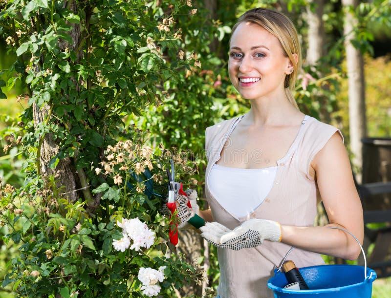Kvinnlig trädgårdsmästare med ett hjälpmedel, stående yttersida i gården royaltyfri bild