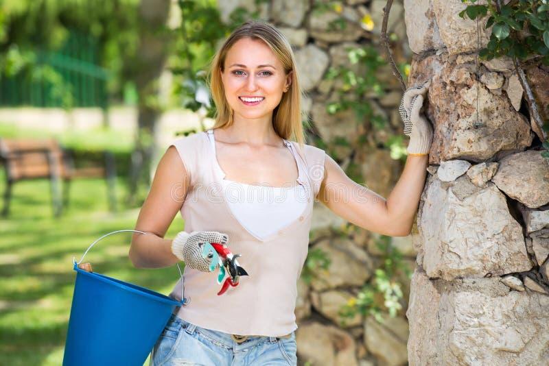 Kvinnlig trädgårdsmästare med funktionsdugliga hjälpmedel utomhus fotografering för bildbyråer