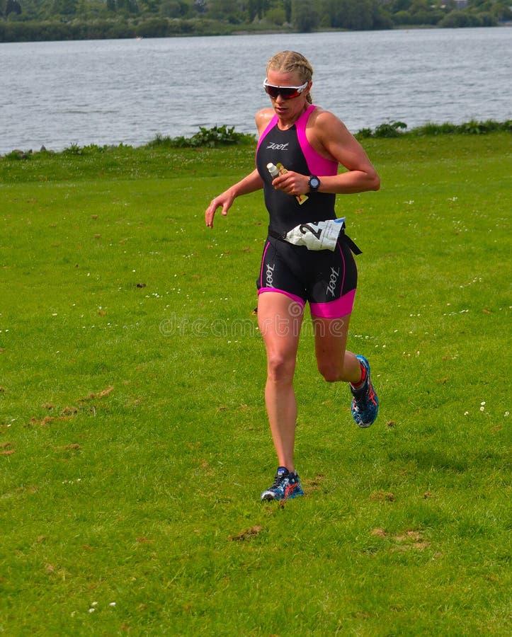 Kvinnlig triathlete på springetapp av triathlonen, bärande loppdräkt fotografering för bildbyråer