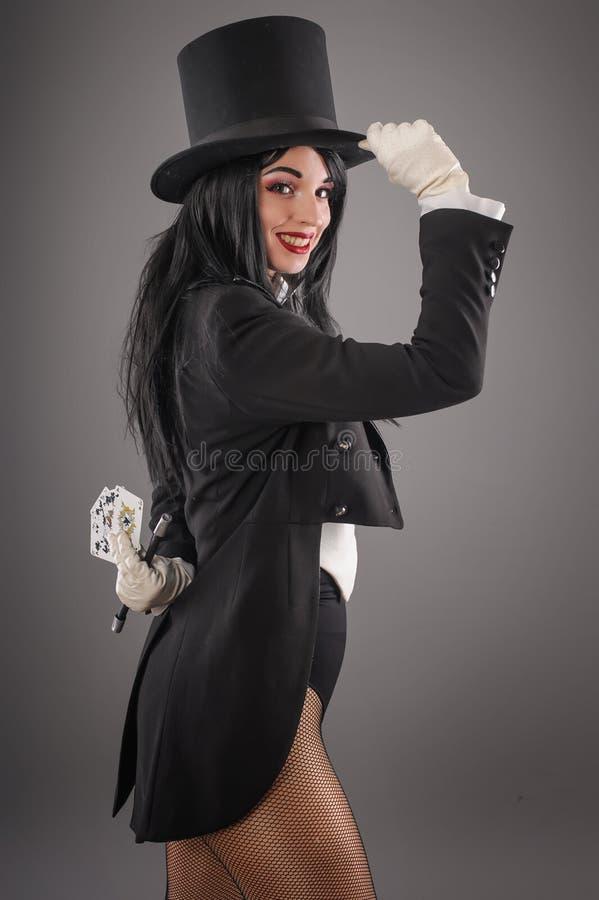 Kvinnlig trollkarl i aktördräkt med trollspöet och spelaca royaltyfri fotografi
